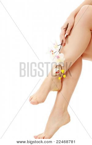 Beautiful female legs with an orchid flower, isolated on white