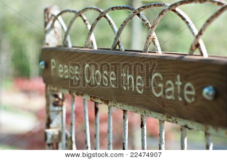 Please Open The Gate Sign On An Iron Gate With Wood