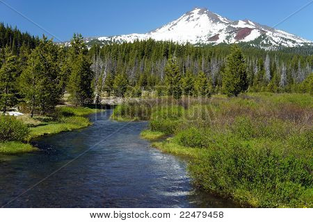 a mountain stream runs off a snow-capped peak