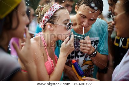 SAMARA,RUSSIA- JULY 24: young people throwing water at each other during Water Wars flash-mob , wet girls and young man taking a break and smoking a cigarettes , July 24, 2011, Samara, Russia