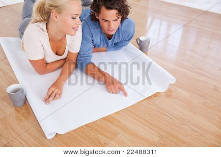 Young Couple Looking At Their Future Room On A Plan