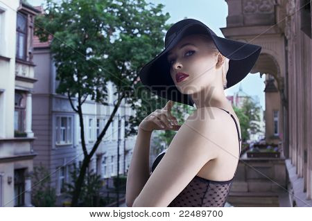 Young Blond Fashion Woman In Elegant Black Hat  In Urban Background