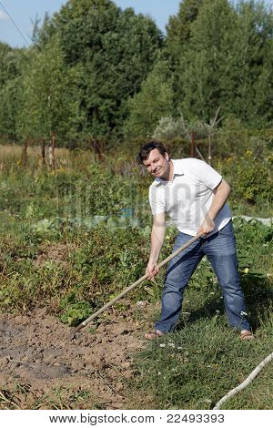 Man Poses With Rake