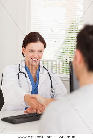Female Doctor Hand Shaking With A Patient