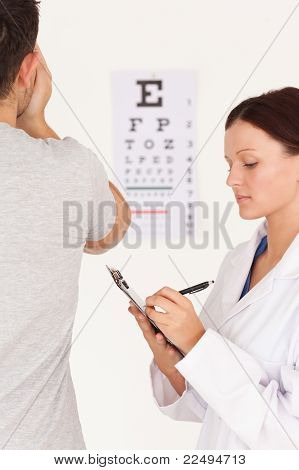 Female Optician Testing Eyes Of A Man