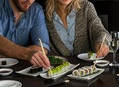 Couple eat sushi rolls on restaurant table. Holding sushi chopstick poster