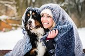 Woman and her dog getting warm on cold winter day under a blanket snuggling poster
