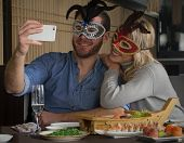 Carnival selfie couple at sushi restaurant wearing carnival mask. poster