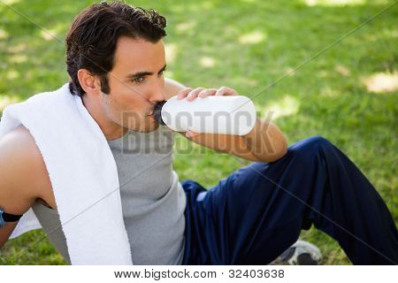 Man with a white towel on his shoulder looking straight ahead while drinking from sports bottle as he sits on the grass