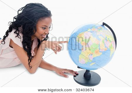 A young smiling girl is pointing at a globe against a white background