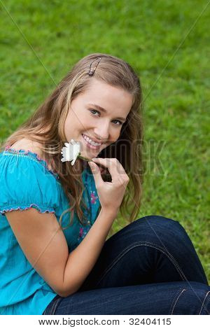 Smiling young girl holding a flower next to her face while sitting in a park