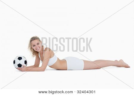 Smiling woman lying down while holding a football against a white background
