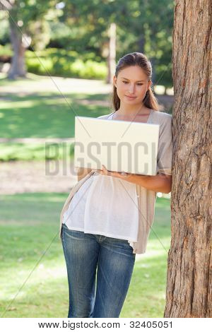 Young woman using a laptop while leaning against a tree