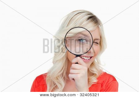 Woman looking through a magnifying glass while showing a blink of an eye