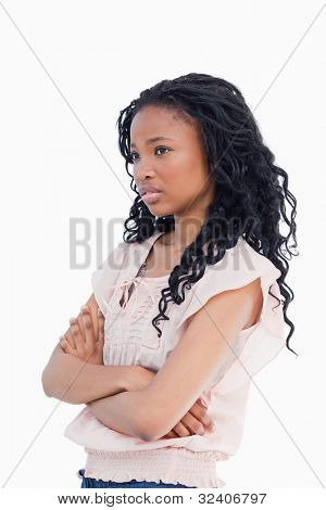 A worried looking girl has her arms folded against a white background