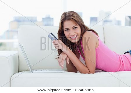 Young woman lying on a sofa in front of her laptop holding her credit card