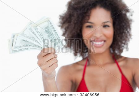 Bank notes being held by an attractive woman against a white background