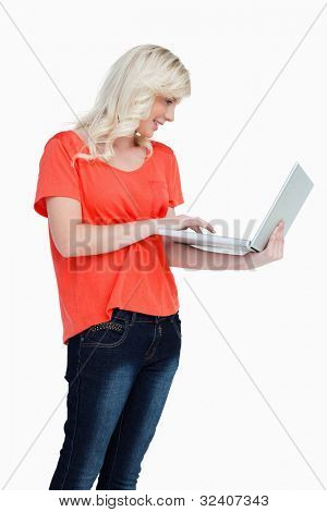 Woman using the touch pad of her laptop against a white background