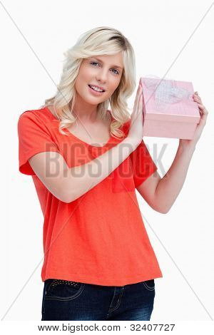 Young woman proudly holding her birthday gift against a white background