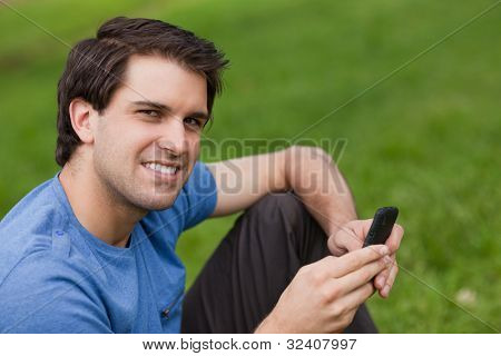 Happy young man looking at the camera while sending a text and sitting on the grass