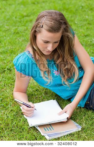 Serious student lying on the grass in the countryside while writing on a notebook