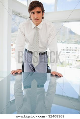 A young serious businessman is leaning on a table