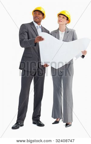 A businessman and woman wearing hard hats and holding a paper are looking up