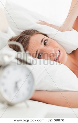 A close up shot of the woman with a pillow over her ears to drown out the alarm.