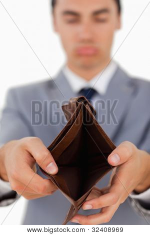 Sad man in a suit showing his empty wallet against white background