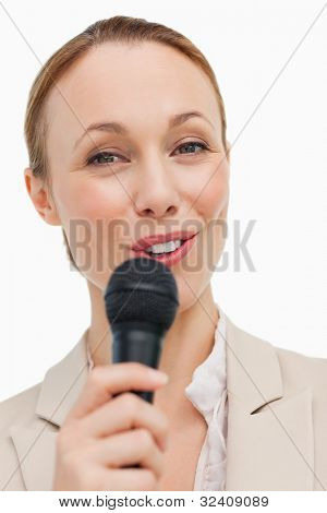 Portrait of a woman in a suit speaking with a microphone against white background