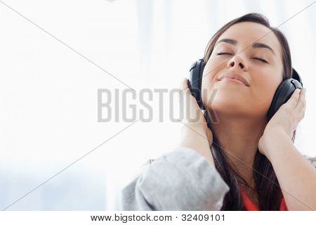 A woman listening to music on her headphones and enjoying it.