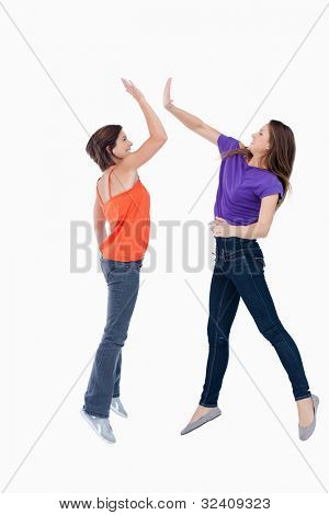 Smiling teenagers jumping while trying to high-five each other in the air