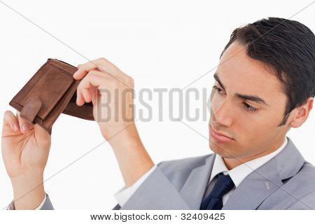 Man in a suit with his wallet empty against white background