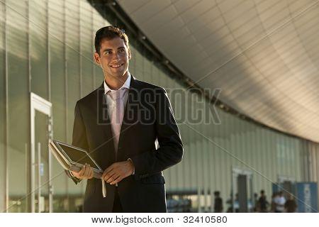 Elegante joven empresario con su tablet PC mientras camina