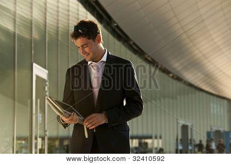 Elegante junge Geschäftsmann mit seinem Tablet PC während des Gehens