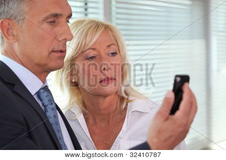 A team of business professionals reading a text message