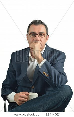 Businessman Holding A Cup Of Tea Sitting In A Chair. Isolated On White Background