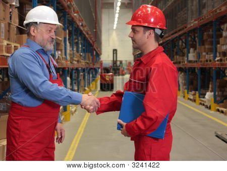 Supervisor And Older Worker Handshake In Warehouse