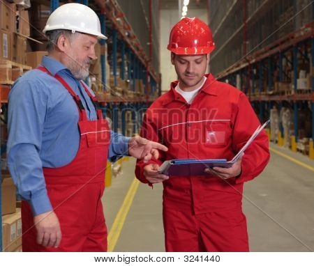 Two Workers In Uniforms In Warehouse