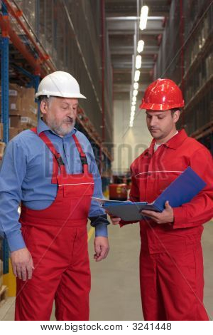 Engineer And Senior Worker Reading Document In Warehouse
