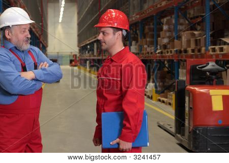 Young And Older Workers Chat In Warehouse