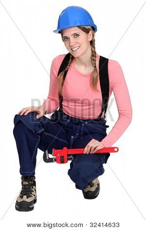 portrait of young female electrician holding spanner