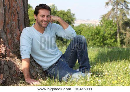 Man sitting against tree