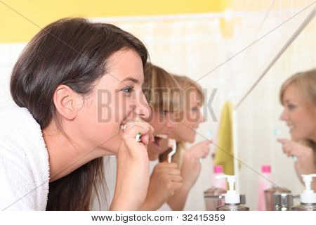 Three young women brushing teeth