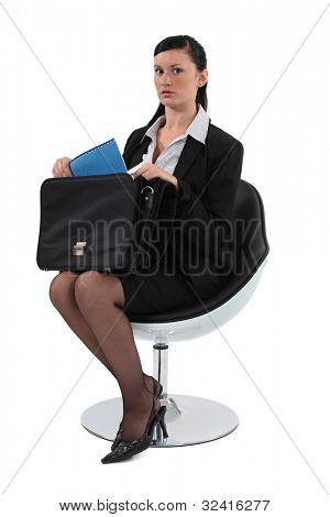 Businesswoman pulling out a document from her briefcase