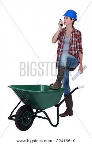 Female foreman with wheelbarrow and radio