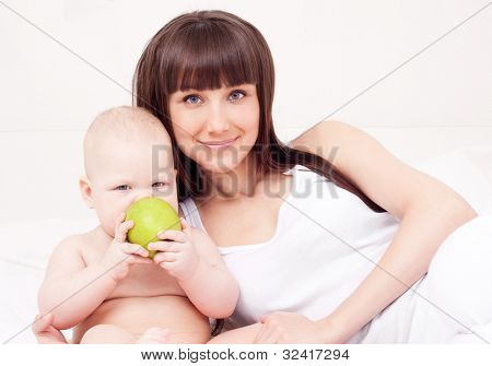 beautiful  young woman  holding her baby eating an apple at home