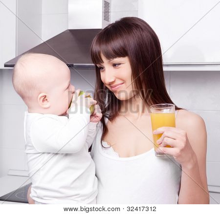 beautiful  young woman drinking orange juice and holding her baby eating an apple in the kitchen