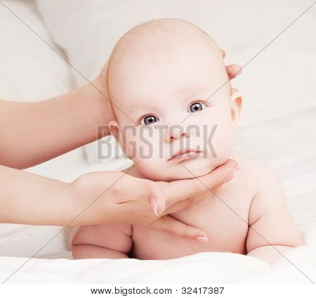 Mother massaging her four month old baby in bed at home