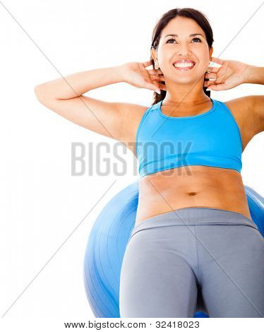 Woman exercising her abs on a Pilates ball - isolated over white